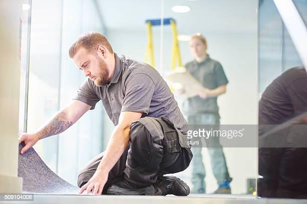 male carpet fitter fitting office carpet tiles