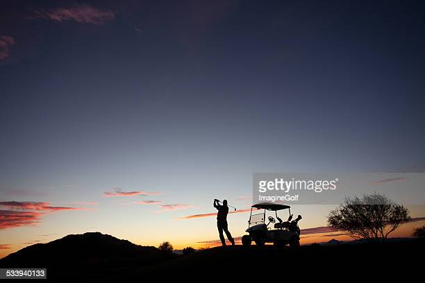 Male Caucasian Golfer Swinging A Golf Club with Cart