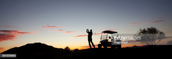 Male Caucasian Golfer Swinging A Golf Club with Cart