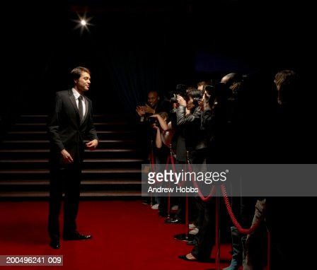Male celebrity in tuxedo standing on red carpet in front of paparazzi : Stock Photo