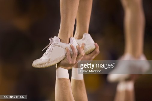 Male cheerleader lifting female cheeleader above his head, close-up