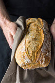 Male chef baker holds in hands in grey cotton towel freshly baked homemade loaf of bread. Authentic style. Mediterranean French cuisine panification