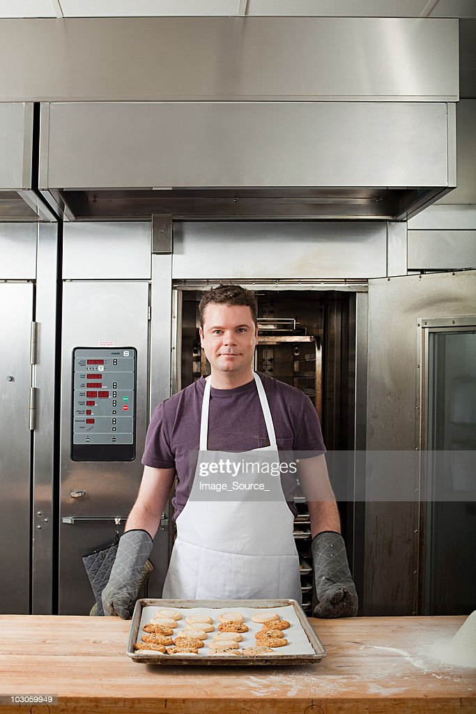Male chef baking cookies in commercial kitchen : Stock Photo