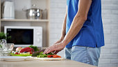 Male chef cutting green salad leaves with kitchen knife for healthy dinner, stock footage