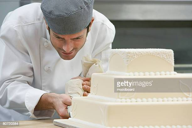 Male chef icing wedding cake in kitchen