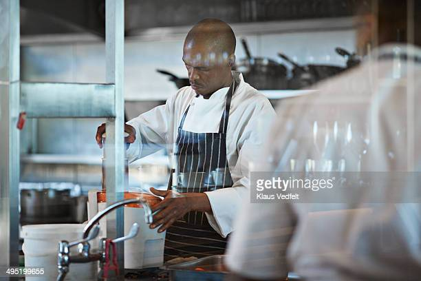 Male chef making veg juice at restaurant