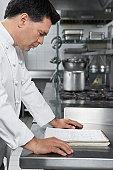 Male chef reading recipe book in kitchen