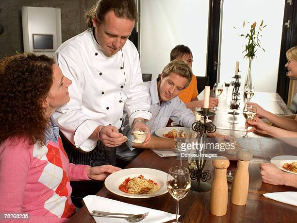Male chef serving parmesan to a young woman at the dining table