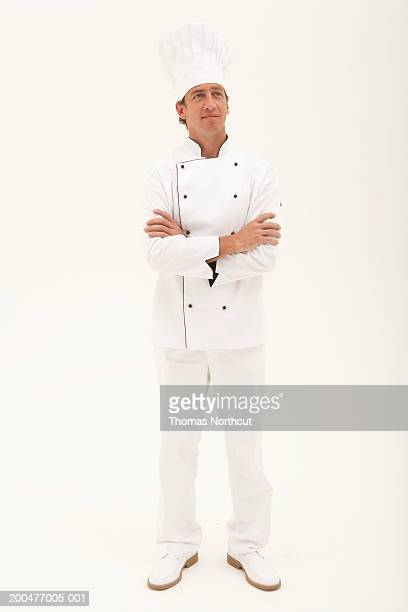 Male chef standing with arms crossed, looking up