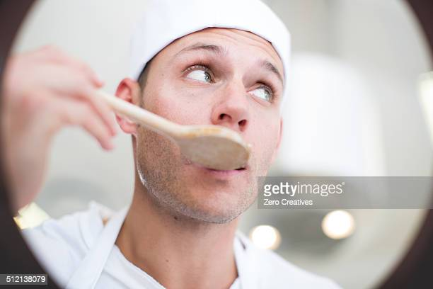Male chef tasting food from saucepan in commercial kitchen