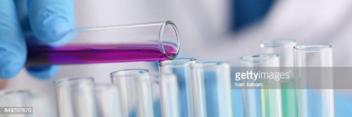Eine männliche Chemiker hält Reagenzglas aus Glas in seiner Hand Überläufe : Stock-Foto