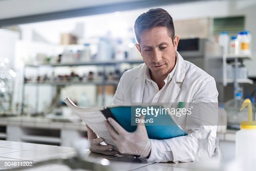 Male chemist reading medical data in laboratory.