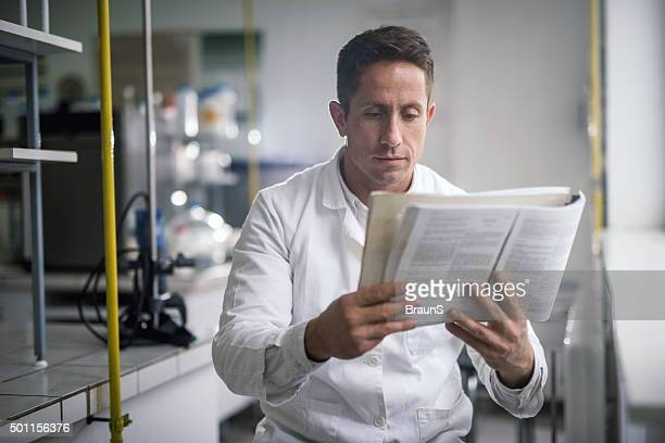 Male chemist reading scientific data from a book.
