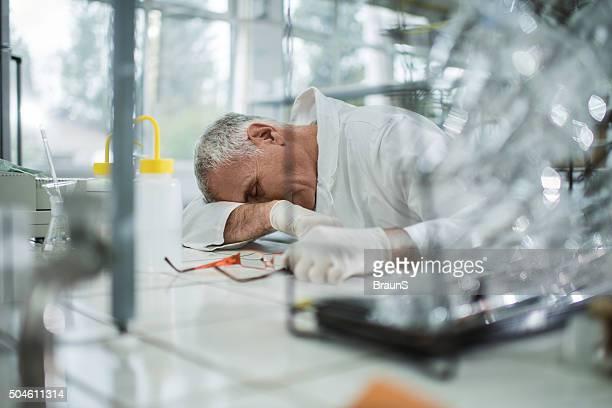 Männliche Chemiker schlafen im Labor nach harten Arbeit.