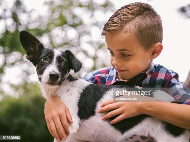 Männliche Kind streicheln den Hund Freund, einen Simplere Welpe Hund