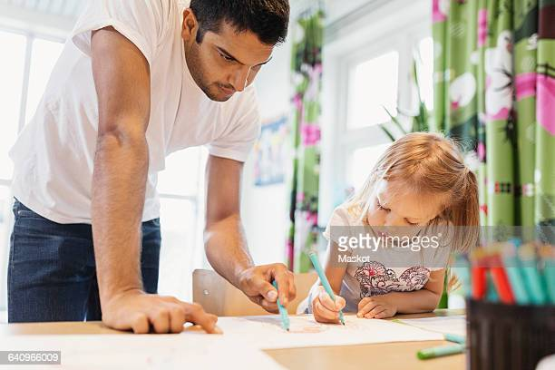 Male children assisting little girl in drawing at classroom