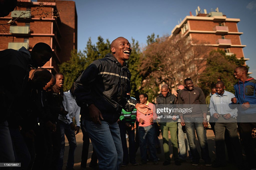 A male choir sing and dance as people gather to pay tribute to Former South African President Nelson Mandela at the memorial wall at the Medi-Clinic Heart Hospital on July 6, 2013 in Pretoria, South Africa. Mandela has been hospitalized at the Medi-Clinic Hospital since June 8 in treatment for a recurring lung infection.