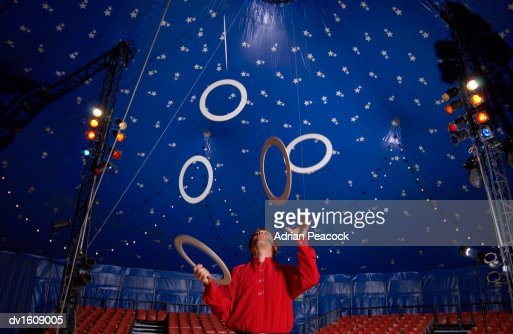 Male Circus Performer Practises Juggling Hoops Inside a Circus Tent : Stock Photo