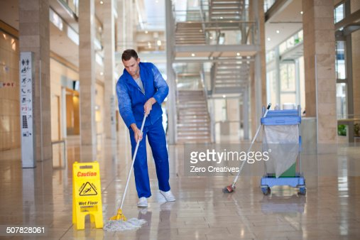 Male cleaner mopping in office atrium