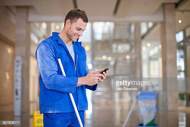 Male cleaner texting on smartphone in office atrium