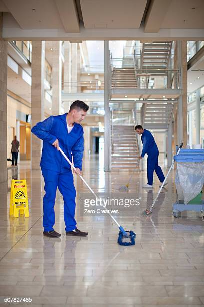 Male cleaners mopping in office atrium