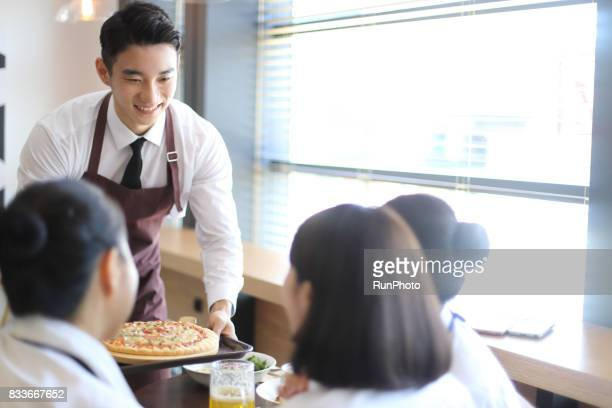 Male clerk at restaurant restaurant bringing pizza ordered
