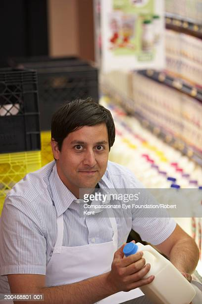 Male clerk putting milk jugs in dairy section in supermarket, portrait