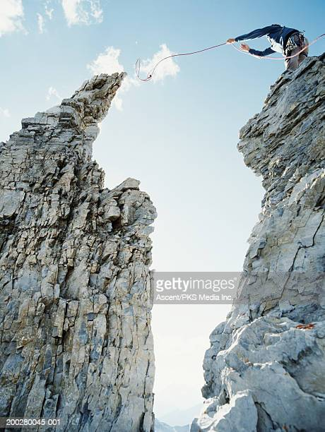Male climber trying to lasso peak of rock, low angle view