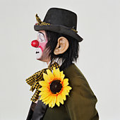 Male clown wearing hat and sunflower, profile