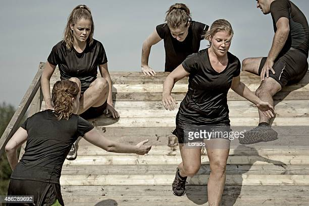 male coach helping women to cross wooden wall obstacle