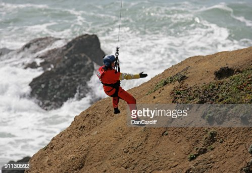 A male coast guard hanging over the ocean