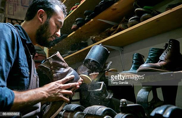 Male cobbler in traditional shoe workshop repairing boot heel