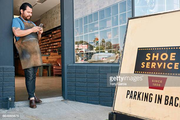 Male cobbler leaning against shoe shop doorway reading smartphone texts