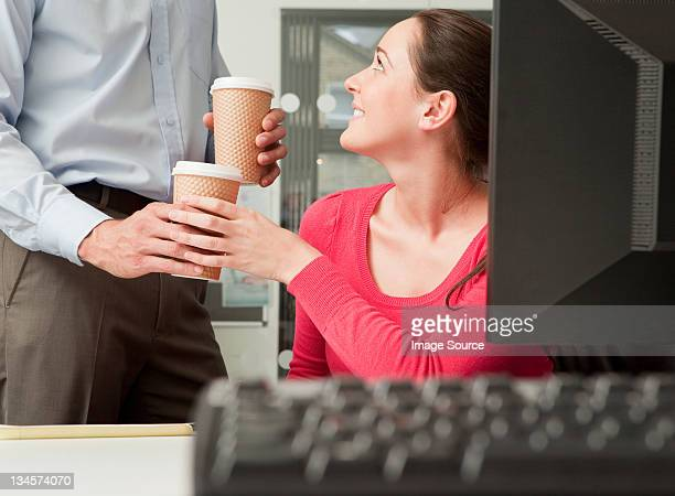Male colleague bringing female colleague coffee