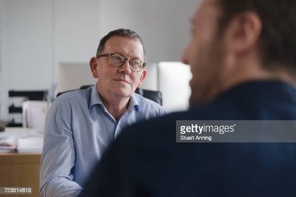 Male colleagues in discussion at office desk