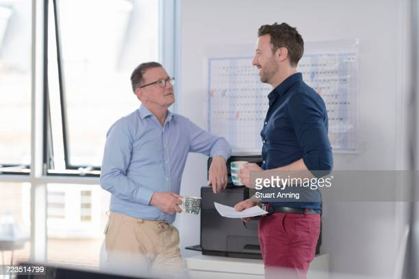 Male colleagues talking by photocopier machine
