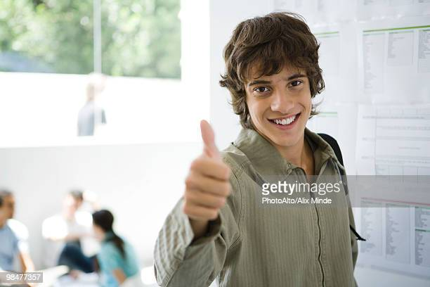 Male college student giving thumbs up, bulletin board in background