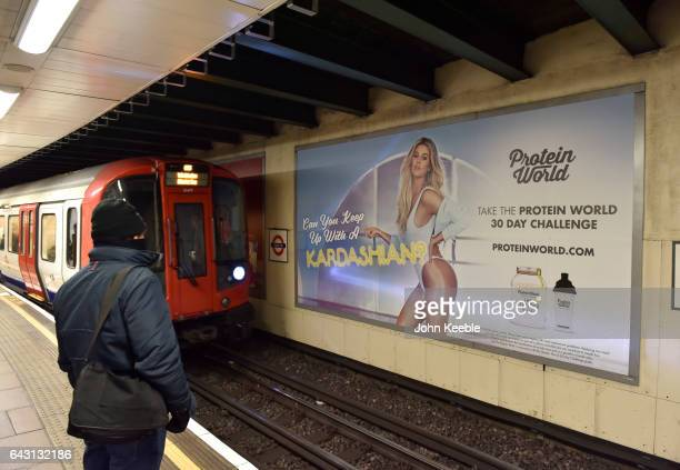 A male commuter stands on the platform at Tower Hill underground station opposite a Protein World advertising poster featuring Khloe Kardashian on...