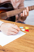 male composer hands writing song on blank white paper with acoustic guitar