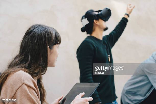 Male computer programmer gesturing while using VR glasses by colleagues in office