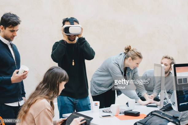Male computer programmer using VR glasses while colleagues working in office