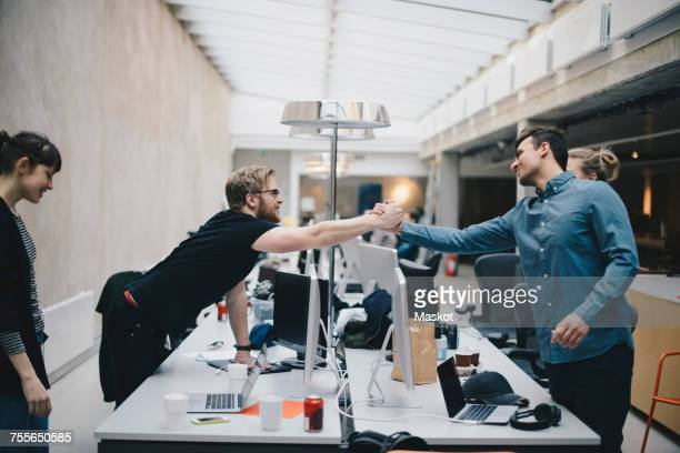 Male computer programmers holding hands over desk in office