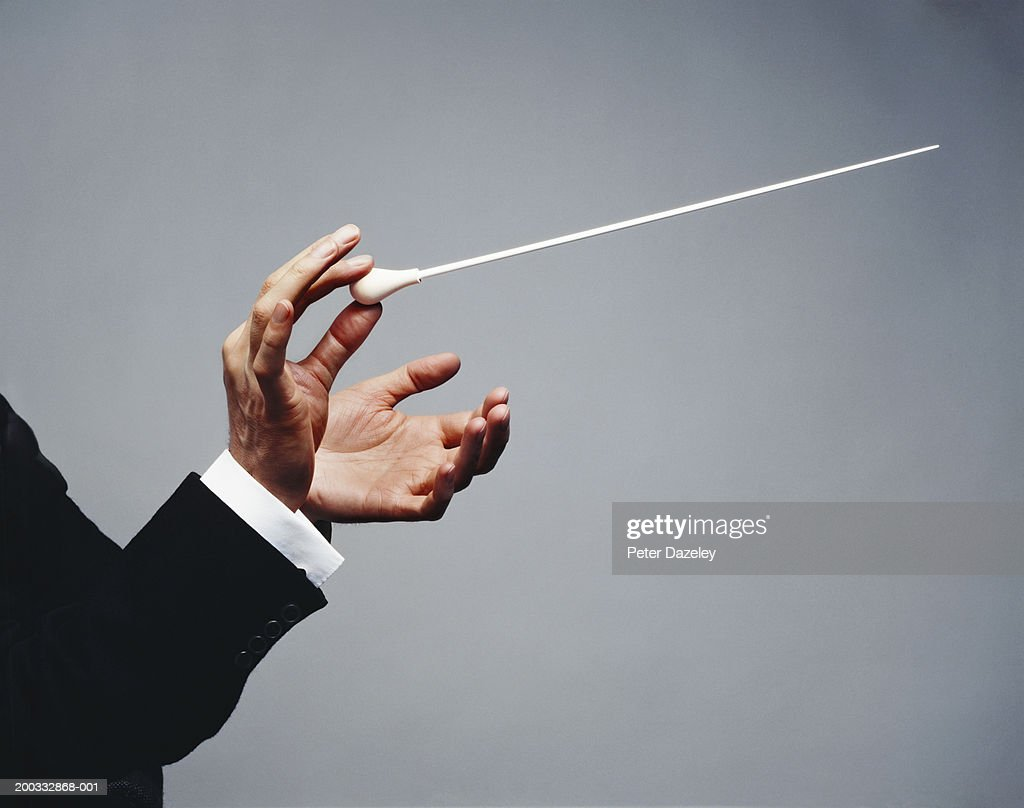 Male conductor holding baton, close-up of hands : Stock Photo