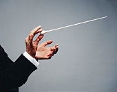 Male conductor holding baton, close-up of hands