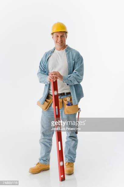 Male construction worker holding level