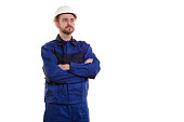 male construction worker in a helmet stands with his arms crossed isolated on white