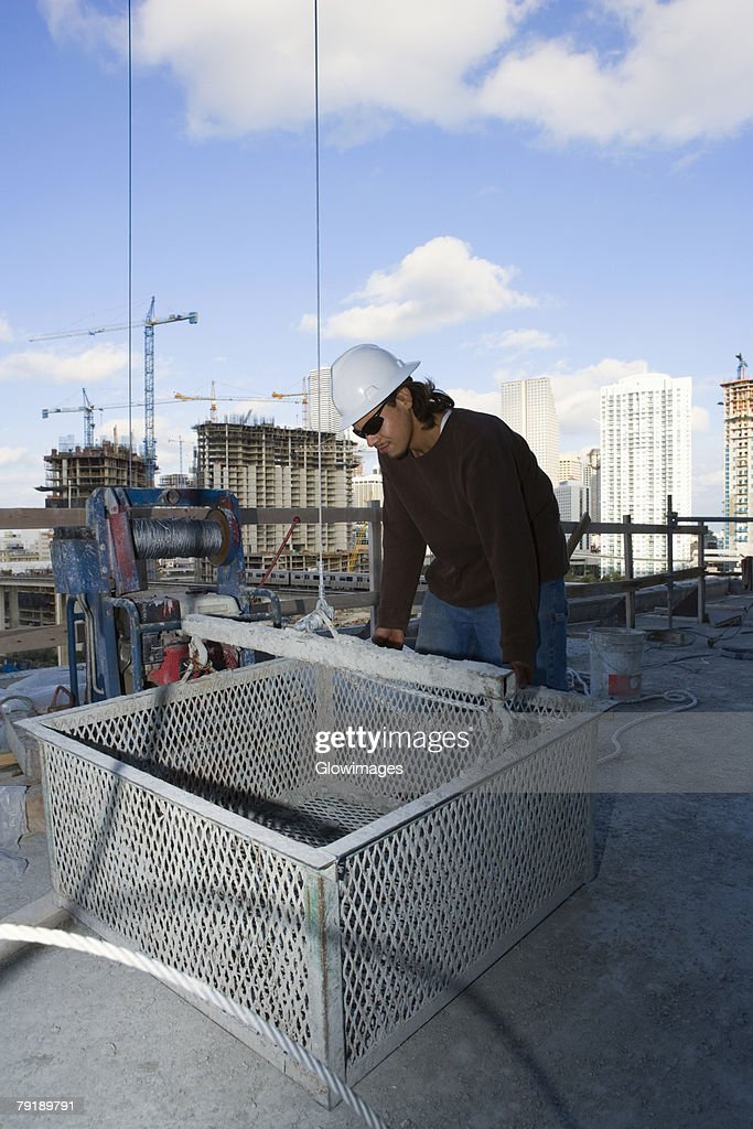 Male construction worker leaning against a basket at a construction site : Stock Photo