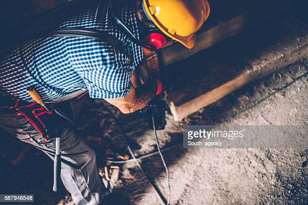 Male construction worker with a drill