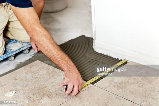 Male Contractor Installing Floor Tiles