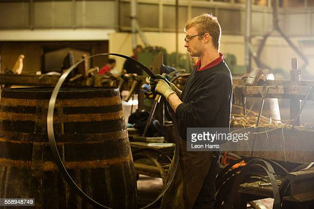 Male cooper making whisky casks in cooperage
